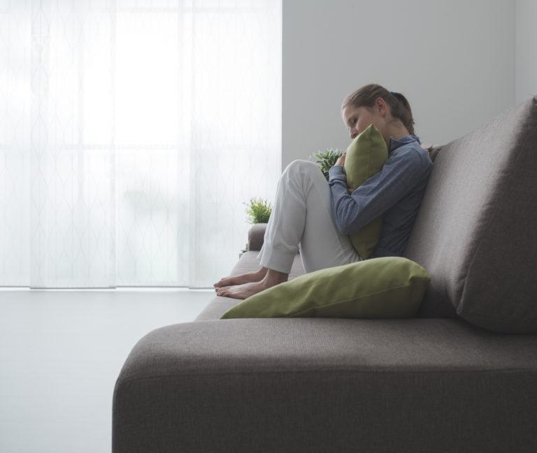 mujer triste agarrando un cojín sentada en el sofá en una habitación oscura