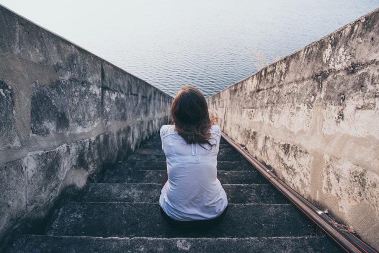 mujer pelirroja vestida de blanco de espaldas en unas escaleras mirando al mar al horizonte