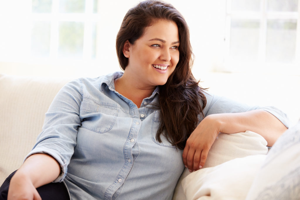 mujer morena obesa feliz vestida de camisa vaquera en un sofá pensando