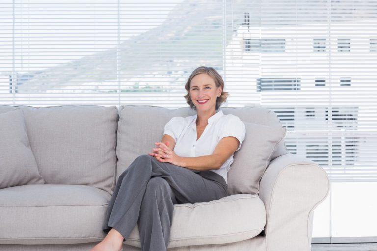 mujer mayor psicóloga sentada en un sofá gris