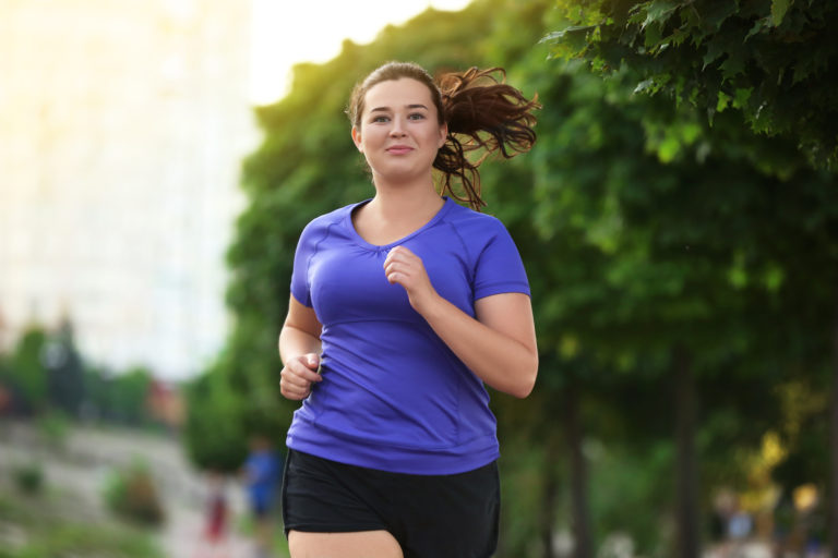 mujer obesa vestida de azul corriendo en la calle feliz disfrutando de la naturaleza