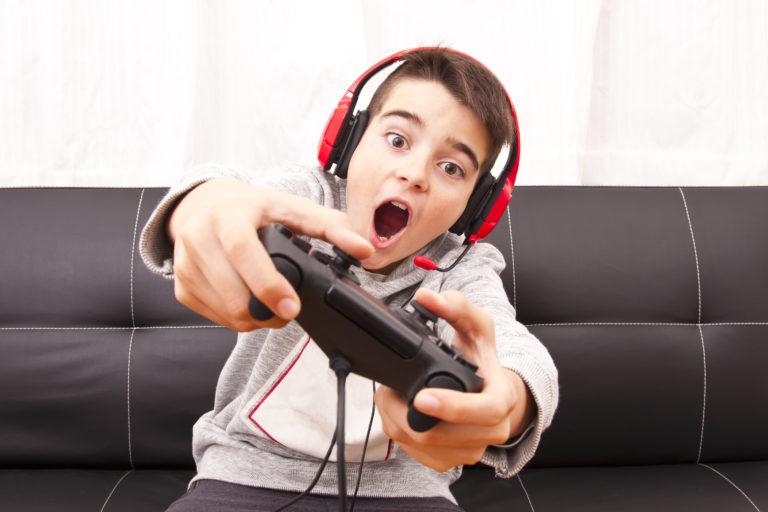 niño jugando a la consola con mando de playstation y cascos en un sofá negro