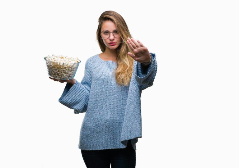 mujer rubia joven vestida de azul comiendo palomitas con fondo blanco