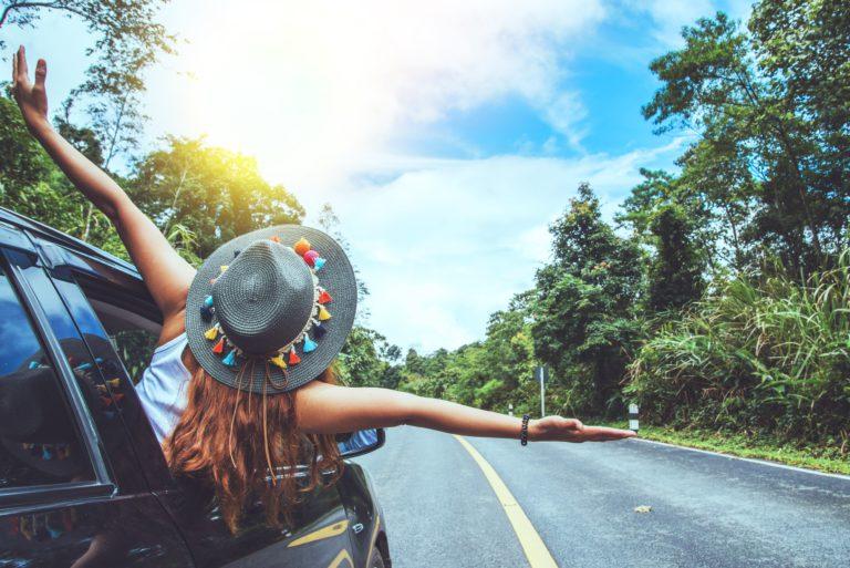 mujer con sombrero sacando el cuerpo por la ventanilla del coche levantando los brazos y mirando al cielo con mucha felicidad en una carretera con mucha naturaleza